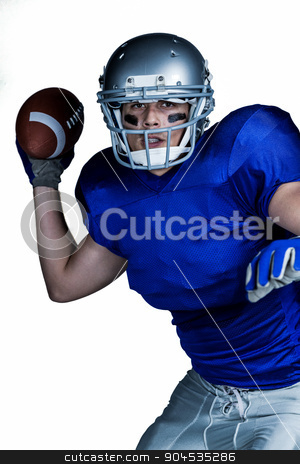 American football player in uniform throwing ball stock photo, Portrait of American football player in uniform throwing ball against white background  by Wavebreak Media