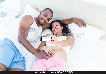 Happy couple clicking selfie while lying on bed stock photo, Happy couple clicking selfie while lying on bed at home by Wavebreak Media