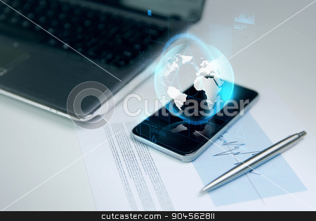 close up of smartphone with earth globe hologram stock photo, business, technology and communication concept - close up of smartphone with earth globe hologram, laptop computer and chart with pen on office table by Syda Productions