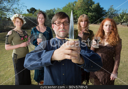 Serious Pagan Priest with Dagger stock photo, Serious male pagan priest with group and dagger outdoors by Scott Griessel