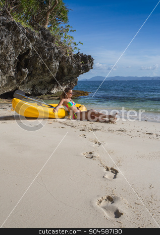 Little girl standing next to colorful yellow kayak  stock photo, Little girl standing next to colorful yellow kayak at tropical beach ready for paddling with her mother or father by Vassiliy Kochetkov