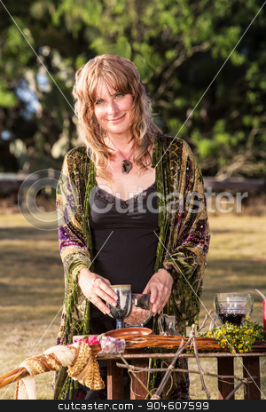 Modern Witch with Goblets stock photo, Smiling adult in outdoor pagan ritual practice by Scott Griessel
