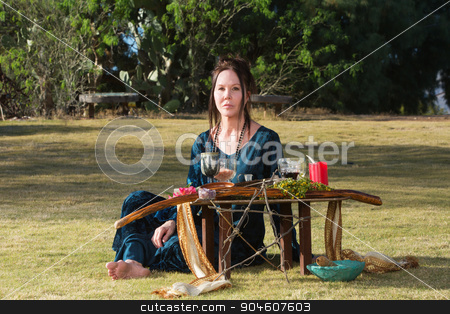 Serious Priestess with Pagan Altar stock photo, Serious priestess in outdoor pagan altar ceremony by Scott Griessel
