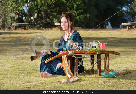 Female with Feathers and Altar stock photo, Caucasian adult outdoors with feather and pagan altar by Scott Griessel