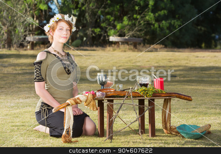 Cute Pagan Woman with Wreath stock photo, Cute pagan woman with wreath sitting at outdoor altar by Scott Griessel