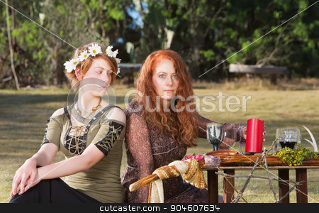 Two Pagans at Altar stock photo, Two serious pagan females sitting at altar with candles by Scott Griessel