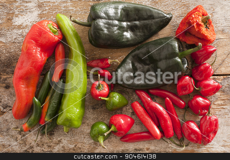 Assortment of Chili Peppers stock photo, A selection of hot Chili Peppers of different varieties and colours on a wooden background by Stephen Gibson