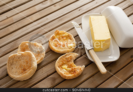 Fresh toasted hot English muffins stock photo, Fresh toasted hot English muffins, one with a bite missing, on a wooden slatted table with a pat of butter in a butter dish by Stephen Gibson