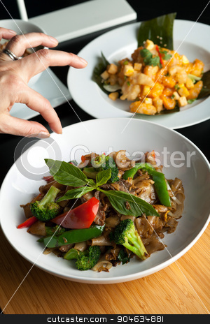 Thai Food Stylist stock photo, Food stylist grooms a dish by adding sweet basil garnish to the traditional thai dish Pad Kee Mao drunken noodle. by Todd Arena