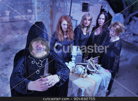 Wicca Priest and Coven in Ritual stock photo, Wicca priest with coven with ritual athame outdoors by Scott Griessel
