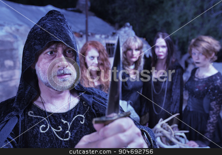 Priest with Witch Coven and Dagger stock photo, Pagan priest with ritual dagger and coven at altar by Scott Griessel