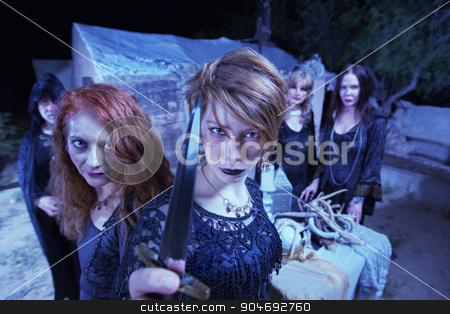 Group of Threatening Witches stock photo, Group of threatening witches in black robes with dagger by Scott Griessel