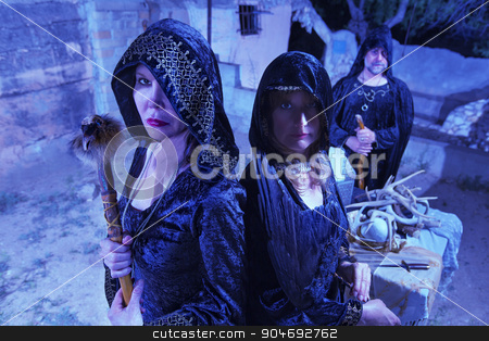 Three Witches in Black stock photo, Group of three witches in black robes near altar outdoors by Scott Griessel
