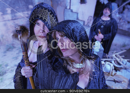 Group of Witches in Black stock photo, Group of witches in black robes near altar outdoors by Scott Griessel
