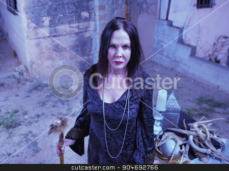Priestess Near Pagan Altar stock photo, Scary priestess with fetish standing near altar by Scott Griessel