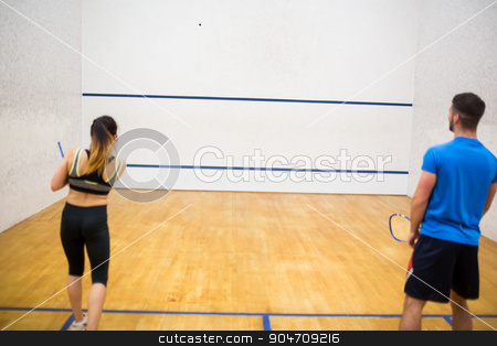 Couple play some squash together stock photo, Couple play some squash together in the squash court by Wavebreak Media