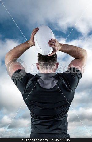Composite image of tough rugby player throwing ball stock photo, Tough rugby player throwing ball against bright blue sky with clouds by Wavebreak Media