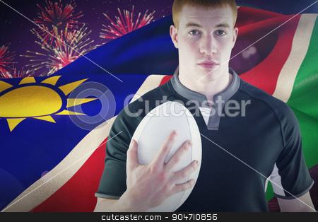 Composite image of rugby player holding a rugby ball stock photo, Rugby player holding a rugby ball against fireworks exploding over football stadium by Wavebreak Media