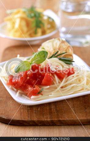 Vegetarian appetizer stock photo, Spaghetti, peeled tomato and baked garlic - closeup by Digifoodstock