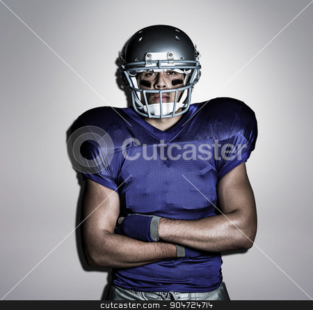 Composite image of portrait of determined american football play stock photo, Portrait of determined American football player with arms crossed against grey background by Wavebreak Media