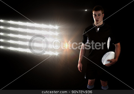 Composite image of rugby player holding a rugby ball stock photo, Rugby player holding a rugby ball against spotlights by Wavebreak Media