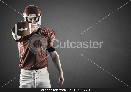 Composite image of portrait of american football player showing football to camera stock photo, Portrait of american football player showing football to camera against green by Wavebreak Media
