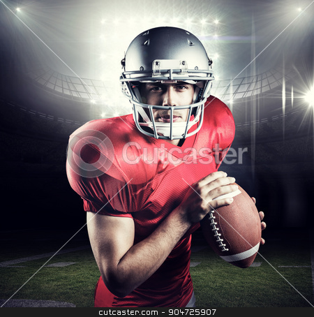 Composite image of portrait of determined sportsman holding amer stock photo, Portrait of determined sportsman holding American football against american football arena by Wavebreak Media