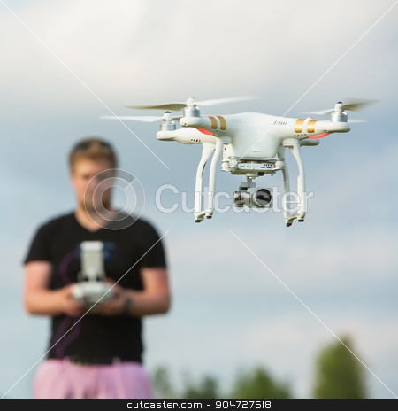 Person Flying a Camera Drone stock photo, Person behind a surveillance camera with remote control by Scott Griessel