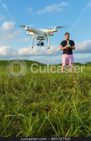 Man Controlling Drone stock photo, Single man in pink pants controlling drone outdoors by Scott Griessel