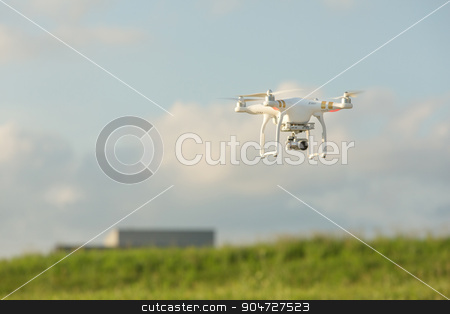 Camera Drone Flying in Sky stock photo, Camera drone quadrocoptor in mid air near building by Scott Griessel