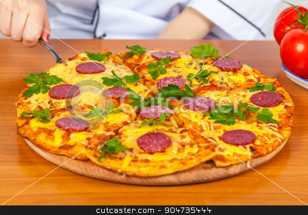 chef holds a slice of pizza stock photo, chef holds a slice of pizza on the blade by MegaArt