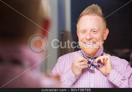Man Tying Bow-tie stock photo, Happy European man with beard tying a bowtie by Scott Griessel