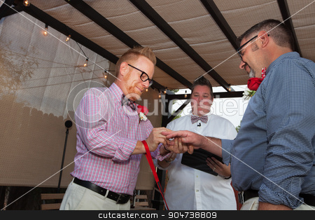 Happy Couple Getting Wedding Rings stock photo, Minister with gay male couple putting on wedding rings by Scott Griessel