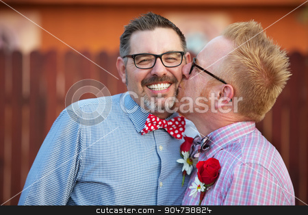 Smiling Man Kissed By Spouse stock photo, Smiling man with eyeglasses being kissed by spouse by Scott Griessel