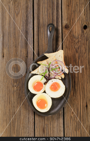 Fried eggs and bread stock photo, Fried eggs and white bread on a skillet by Digifoodstock