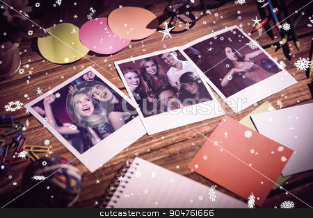 Composite image of high angle view of office supplies with blank stock photo, High angle view of office supplies with blank instant photos against happy friends having fun together by Wavebreak Media