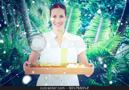 Composite image of snow stock photo, Snow against smiling beauty therapist holding tray of beauty treatments by Wavebreak Media
