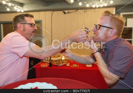 Gay Men Share Cake stock photo, Gay male couple share bacon cupcake at their wedding  by Scott Griessel