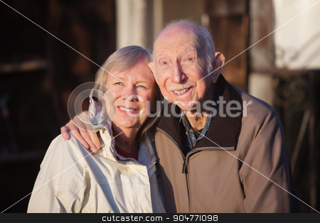 Man and Woman Standing Close stock photo, Cute elderly Caucasian couple in jackets smiling outdoors by Scott Griessel