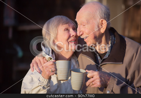 Senior Woman Kissing Husband stock photo, Happy senior woman with coffee kissing husband by Scott Griessel