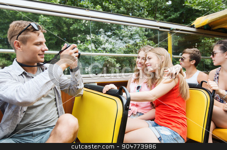 happy friends with camera traveling by tour bus stock photo, friendship, travel, vacation, summer and people concept - group of happy friends with digital camera traveling by tour bus and photographing by Syda Productions