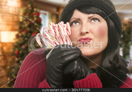 Woman Holding Candy Canes in Christmas Setting stock photo, Pretty Woman Holding A Bunch of Candy Canes in Christmas Setting. by Andy Dean