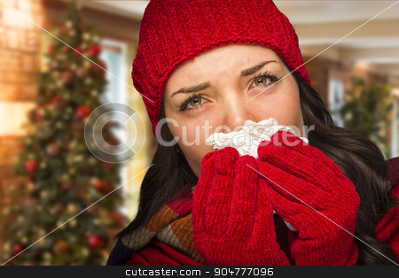Sick Woman Blowing Her Nose With Tissue In Christmas Setting stock photo, Sick Mixed Race Woman Blowing Her Sore Nose With Tissue In Christmas Setting. by Andy Dean
