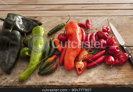 Variety of different chili peppers in a kitchen stock photo, Variety of different chili peppers in a kitchen lying displayed by color on a wooden counter top with a knife waiting to be cut up for cooking by Stephen Gibson