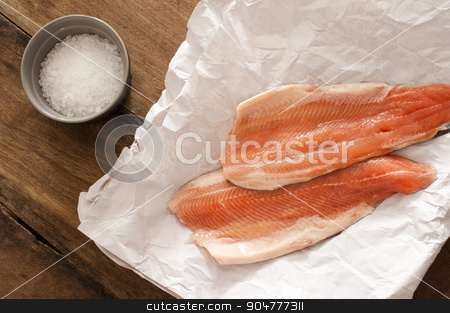 Two raw rainbow trout fillets stock photo, Two gourmet raw rainbow trout fillets lying on crumpled white paper with a ramekin of rock salt alongside waiting to be cooked, overhead view by Stephen Gibson