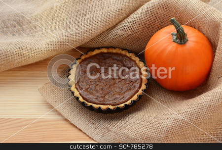 Pumpkin pie and pumpkin in hessian stock photo, Pumpkin pie and autumnal pumpkin nestled in hessian fabric on a wooden table by Sarah Marchant