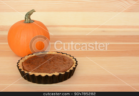 Mini pumpkin pie with orange pumpkin on wood stock photo, Mini pumpkin pie with small orange pumpkin on a wooden background, with copy space by Sarah Marchant