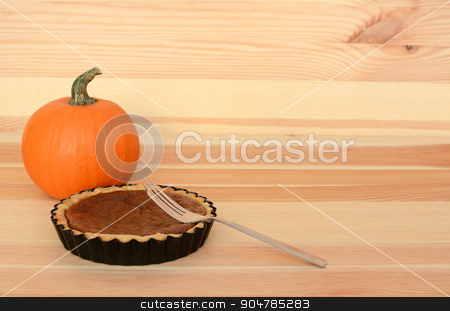 Fork with a small pumpkin pie on wood stock photo, Fork with a small pumpkin pie on a wooden table with small orange gourd, with copy space by Sarah Marchant