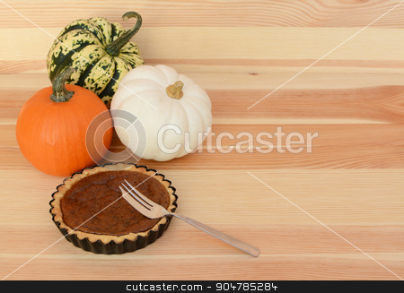 Three pumpkins with small pumpkin pie and fork stock photo, Three mini pumpkins with small pumpkin pie and fork on a wooden table, with copy space by Sarah Marchant