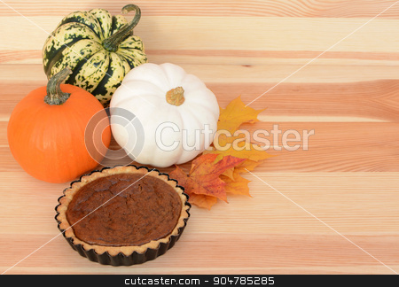 Fall pumpkins and leaves with pumpkin pie stock photo, Autumnal pumpkins and maple leaves with small pumpkin pie on a pine table, with copy space by Sarah Marchant